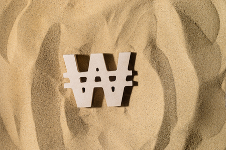 South Korean Won Symbol lies on the Sand in Direct Sunlight 写真素材