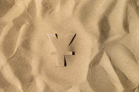 Japanese Yen or Chinese Yuan Symbol or Sign Covered with Sand in the Sun after Crisis