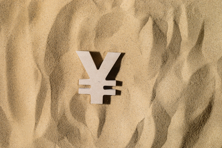 Japanese Yen or Chinese Yuan Symbol lies on the Sand in Direct Sunlight