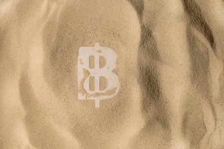 Bitcoin Symbol lies on the Sand in Direct Sunlight