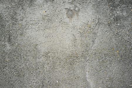 Texture monochromatique du vieux mur de béton patiné avec des fissures et des taches d'eau
