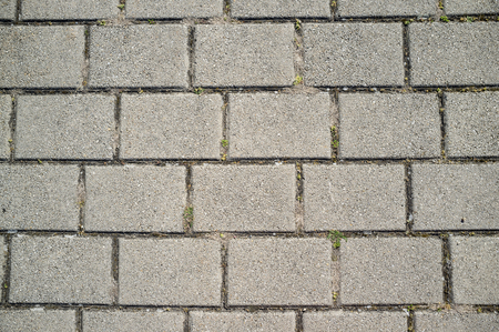 Texture of Concrete Paving Detail with Grass Growing from Cracks