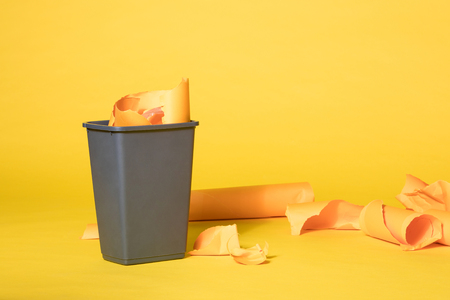 Grey Trash Bin Full with Scrapes of Yellow Paper on Vibrant Yellow Seamless Background Reklamní fotografie