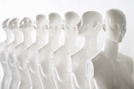 Bright Photo of Plastic Woman Mannequins Standing in The Line, With One Looking to Another Direction then the Others on white Background