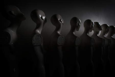 White Woman Torso Figurines Standing in The Line All Looking to Same Direction except of One, shoot in Dark and Dusky Mood. Imagens - 124979501