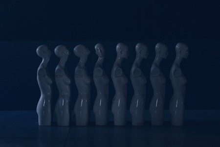 Dark Blue and Moody Photo of Woman Torso Figurines Standing in The Line All Looking to Same Direction except of One