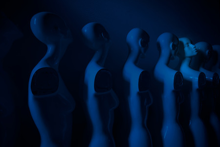 Plastic Woman Mannequins Standing in The Line, With One Looking to Another Direction then the Others all Shoot in dark Blue Melancholic Mood