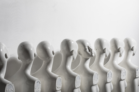 Close Up of White Woman Torso Figurines Standing in The Line All Looking to Same Direction except of One