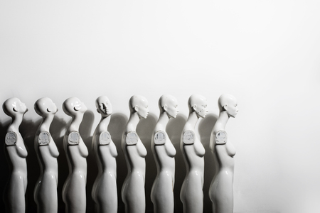 White Woman Torso Figurines Standing in The Line All Looking to Same Direction except of One, Shoot on White Background With Space for Text.
