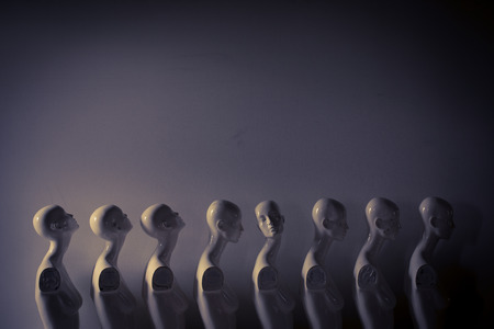 Maniquíes de mujer de plástico de pie en la fila, con uno mirando en otra dirección y luego los demás en estado de ánimo melancólico
