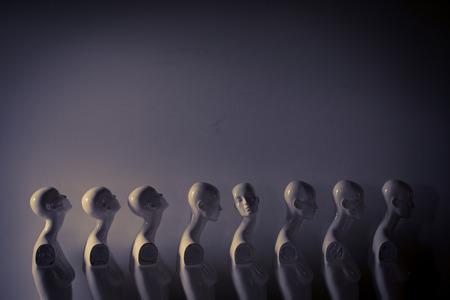 Plastikowe manekiny kobiece stojące w kolejce, z jednym patrzącym w innym kierunku, a potem innymi w melancholijnym nastroju
