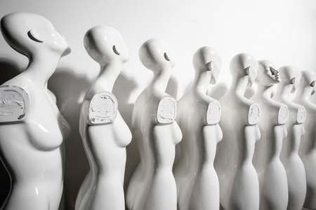 Wide angle Photo of Plastic Woman Mannequins Standing in The Line, With One Looking to Another Direction then the Others