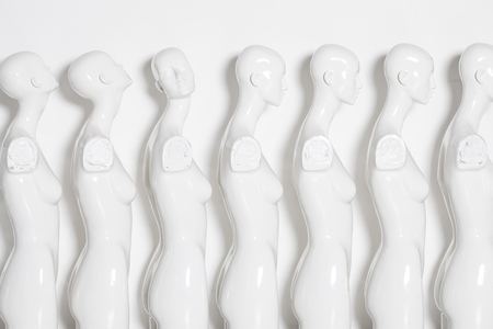 High Key Bright Picture of White Woman Torso Figurines Standing in The Line All But One Looking to Same Direction. Reklamní fotografie