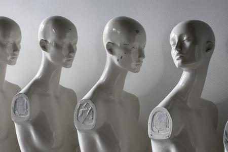 Weiße Frauen-Torsofiguren, die in der Reihe stehen, die alle in die gleiche Richtung blicken, außer einer Standard-Bild