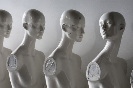 White Woman Torso Figurines Standing in The Line All Looking to Same Direction except of One