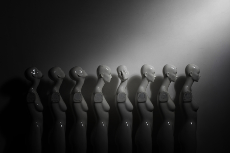 White Woman Torso Figurines Standing in The Line All Looking to Same Direction except of One, shoot in Dark Mood with Spotlight