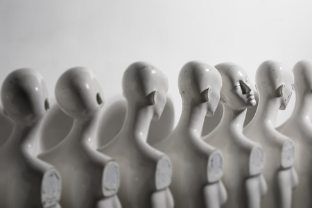 White Woman Torso Figurines Standing in The Line All Looking to Same Direction except of One all shoot on White Bright Background