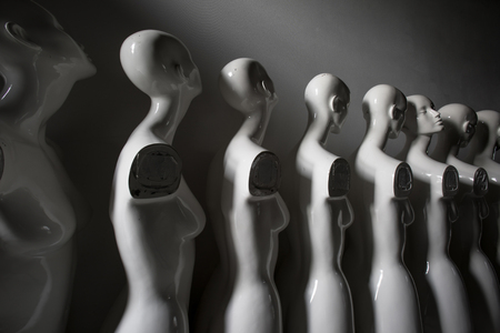 Black and White Photo of Woman Torso Figurines Standing in The Line All Looking to Same Direction except of One