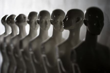 White Woman Torso Figurines Standing in The Line All Looking to Same Direction except of One, Shoot in Closeup and Shallow Focus Фото со стока