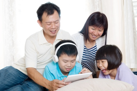 girl bonding: Asian family having fun with tablet computer