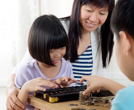 abacus: Azjatycka liczenia monet za pomocÄ… liczydÅ'a dziecko Zdjęcie Seryjne