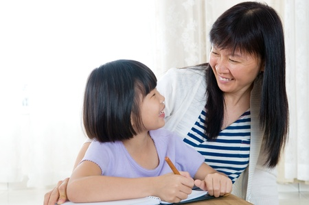 Asian girl writing and talking to her mother photo
