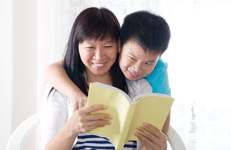Asian woman and her son sharing a book photo