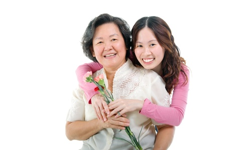 mothers day: Asian woman giving carnation flower to her mother  Stock Photo