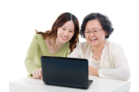asian elderly: asian senior woman learns to use computer