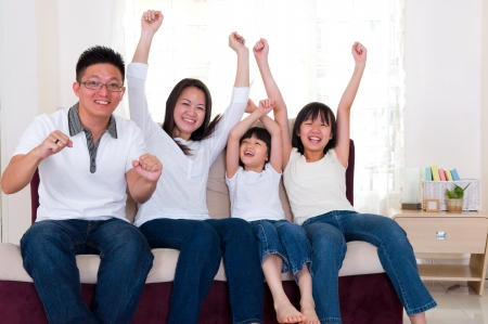 sport fan: Asian family watching television and shouting on their home side in a sporting competition