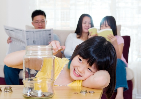 asian coins: Asian girl putting coins into the glass bottle  Money saving concept