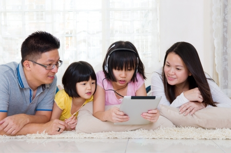 Asian family lying on the floor browsing internet on tablet computer photo