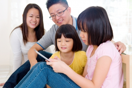 four person: Asian kids browsing internet on tablet computer