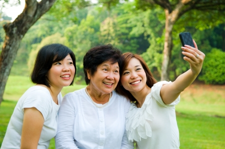 asian family fun: Asian senior woman and daughters taking picture with mobile phone Stock Photo