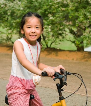 kids exercise: Asian girl riding a bicycle Stock Photo