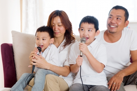 Asian family singing at home Stock Photo