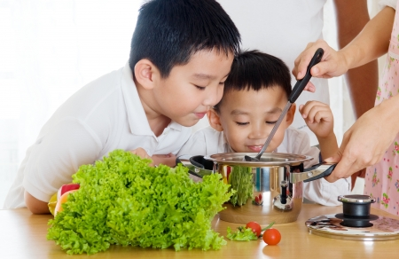 children cooking: asian boys smell their mother s cooking