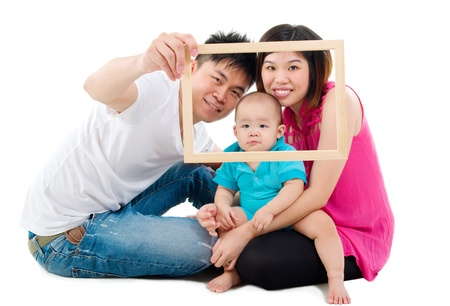 Asian family posing with wooden frame photo