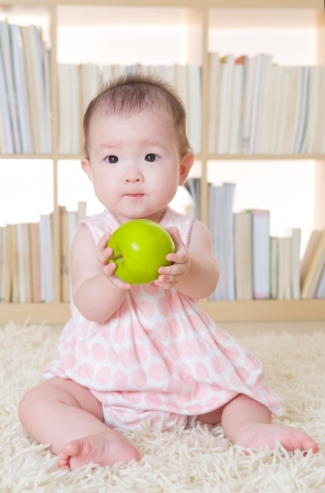 baby girl holding an apple photo