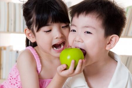 niños comiendo: Niños asiáticas que comparten una manzana