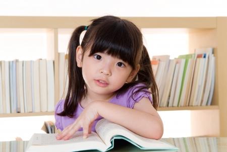 ni�os leyendo: Lectura asi�tica de la muchacha Foto de archivo