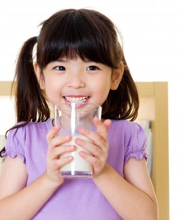 tomando leche: Asia ni�a bebiendo un vaso de leche Foto de archivo