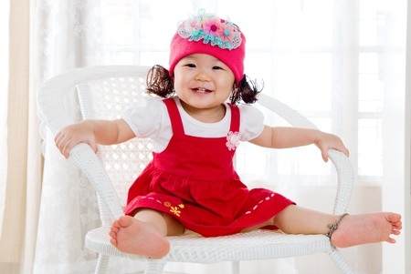 Smiling asian girl sitting on the chair photo
