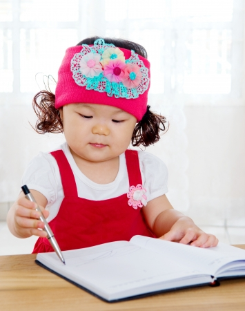 Little asian girl writing photo