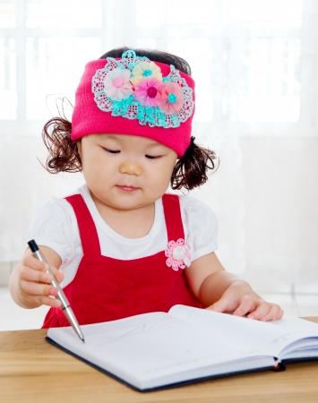 kids writing: Little asian girl writing Stock Photo
