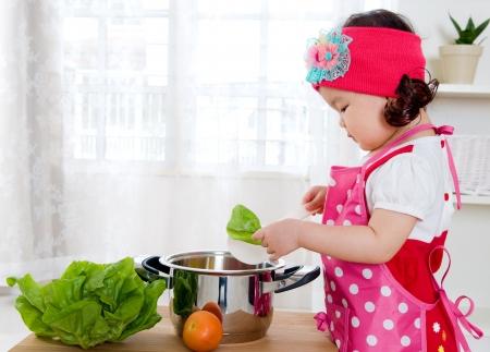 ni�os comiendo: El cocinar de la ni�a