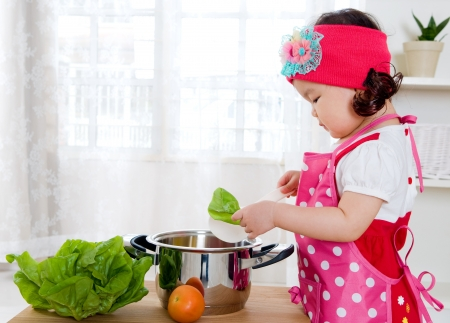 kids eating healthy: Little girl cooking Stock Photo
