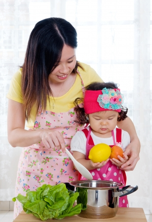 asian baby girl: Asian mother and daugther in the kitchen
