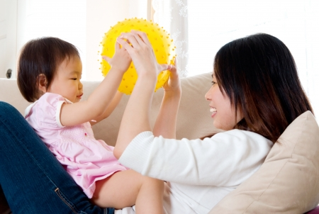 Asian mother playing with her baby girl photo