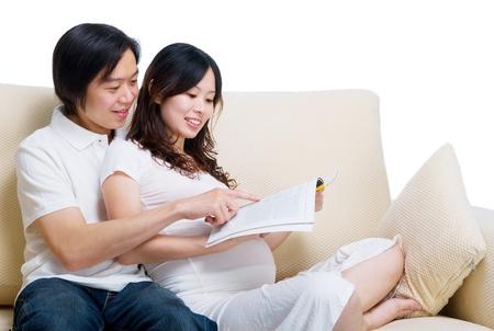 homme enceinte: Asian femme enceinte lisant le magazine avec mari Banque d'images